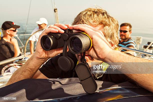 Skipper looking thru binoculars