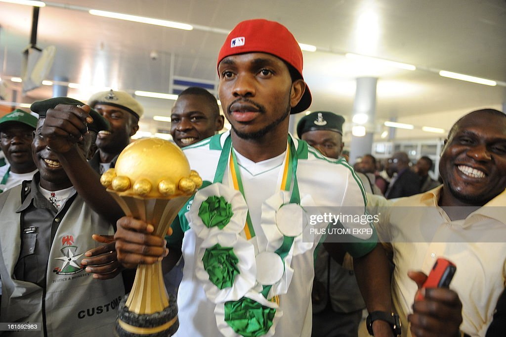 Skipper of Nigerian football team Joseph Yobo (C) holding the Africa Cup of Nations trophy arrives at the airport in Abuja, on February 12, 2013. The newly crowned African champions Nigerian Super Eagles arrives in Abuja to a warm reception by fans and government officials after defeating Burkina Faso to win the 2013 African Cup of Nations in South Africa.