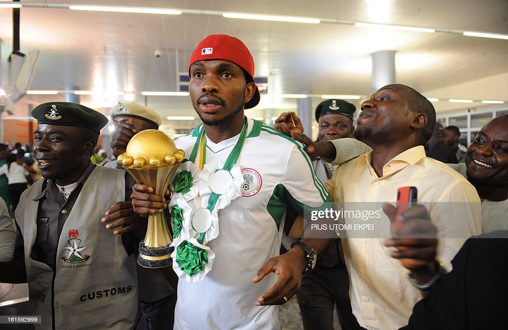 Skipper of Nigerian football team Joseph Yobo (C) holding the Africa Cup of Nations trophy arrives at the airport in Abuja, on February 12, 2013. The newly crowned African champions Nigerian Super Eagles arrives in Abuja to a warm reception by fans and government officials after defeating Burkina Faso to win the 2013 African Cup of Nations in South Africa. AFP PHOTO/ PIUS UTOMI EKPEI