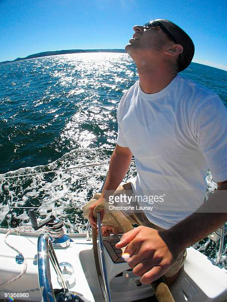 A skipper steering on board a yacht under blue skies while cruising in Pittwater on the North Shore