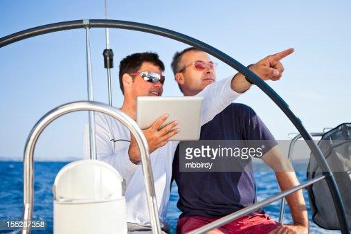 Skipper using digital tablet on sailboat