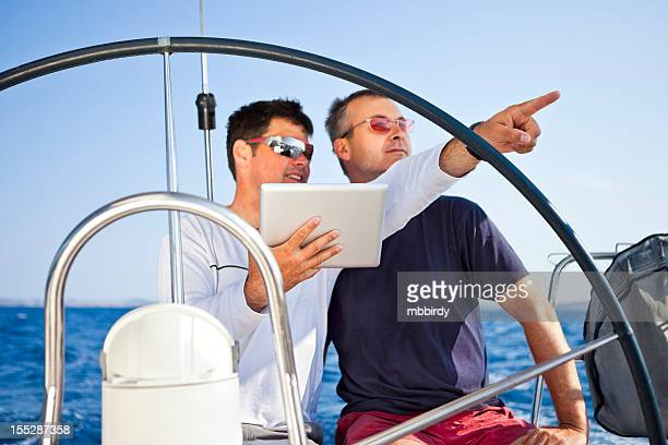 Skipper using digital tablet on sailboat