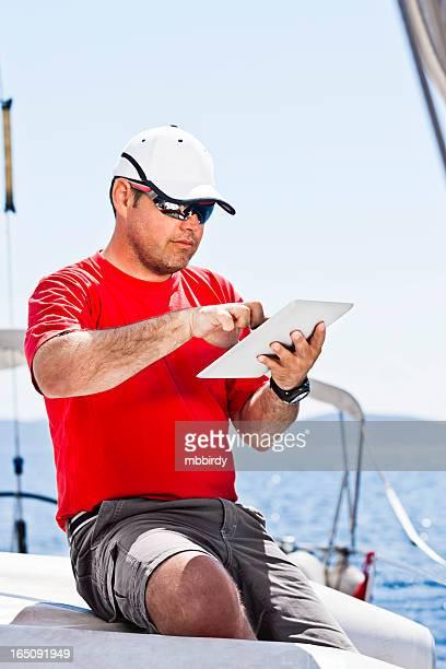 Skipper mit digitalen tablet auf Segelboot