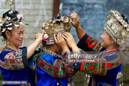 Skirt Miao women putting on traditional headwear