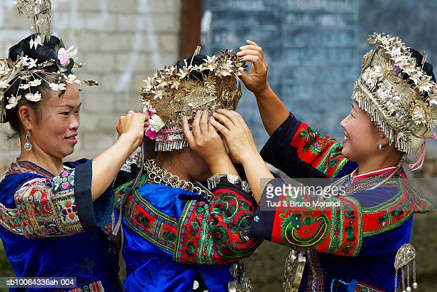 Skirt Miao women putting on traditional headwear