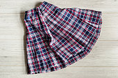 Folded uhiform tartan skirt on wooden background closeup