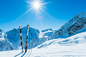 Skis and ski poles on remote slope of ski resort.