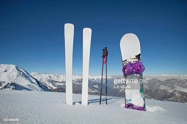 Skis and snowboard stuck in the snow