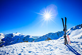 Skis and ski poles on top of slope against sun. Click for more similar images: