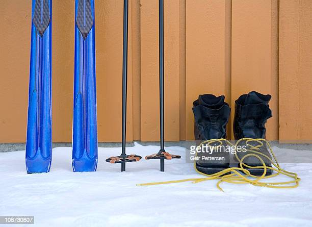 Skis, poles and ski boots by wooden wall