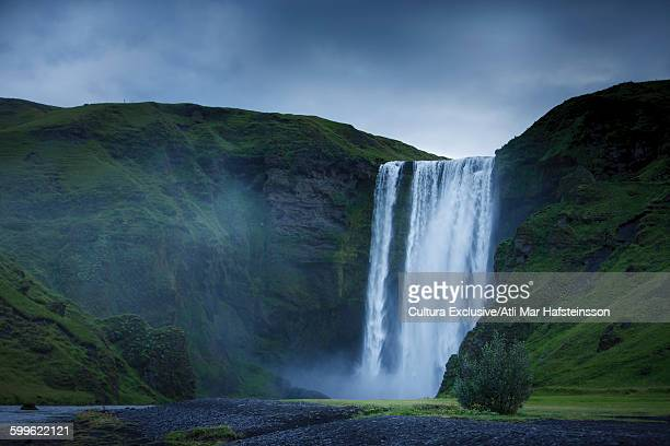 Skogafoss waterfall and grass covered mountains, Rangarvallasysla, Iceland