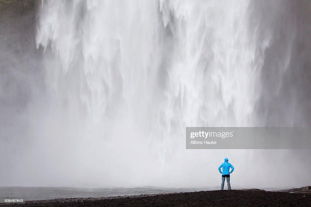 Skogafoss waterfall with a hiker, Skogar, South Iceland, Iceland, Europe