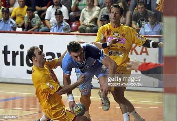 Miladin Kozlina from Slovenia tries to score near the Vladimir Temelkov and Vlatko Mitkov from Macedonia during the men's Handball Euro 2008 second...