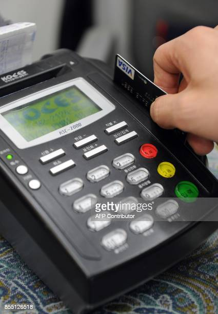SKoreacreditcardretaileconomy FEATURE by Nam YouSun In a picture taken on April 1 2011 a South Korean cashier swipes credit card to a card register...