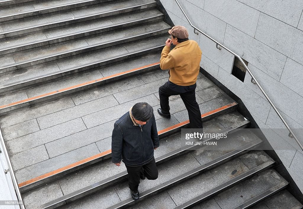 SKorea-economy-debt,FEATURE by Lim Chang-Won People walk up and down stairs at a subway station in central Seoul on February 5, 2013. A mountain of household debt in South Korea, coupled with rising interest rate, is taking a toll on lives of ordinary and low-income families. .