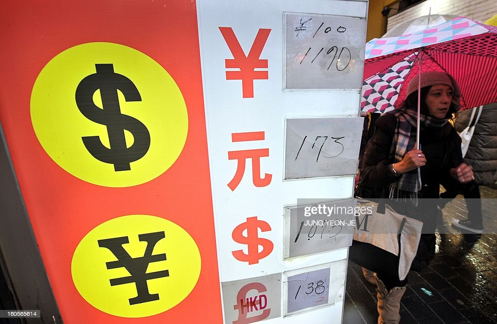 SKorea-Japan-economy-trade-forex,FOCUS by Jung Hawon This photo taken on February 1, 2013 shows a woman walking past a currency exchange sign at a shopping district in Seoul. A surging won and waning yen are eroding the bottom lines of South Korea's export powerhouses who are feeling the pinch after years of gobbling up global market share from their Japanese rivals.