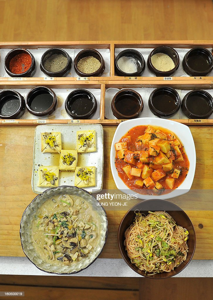 STORY SKorea-religion-Buddhism-food,FEATURE by Park Chan-Kyong This picture taken on November 2, 2012 shows temple foods of tofu sauteed in plum-sauce (L middle), mushroom casserole (L bottom), radish kimchi (R middle), noodles mixed in chilli sauce and vegetables (R bottom) and cruets (top) after a cooking class by South Korean Buddhist monk Jeokmun at his Sudoksa temple in Pyeongtaek City, about 60 kilometers (38 miles) south of Seoul. A centuries-old tradition of Buddhist cuisine, with strict bars on foods linked to lust or anger, is enjoying a revival in South Korea, one of Asia's most high-stress societies. AFP PHOTO / JUNG YEON-JE