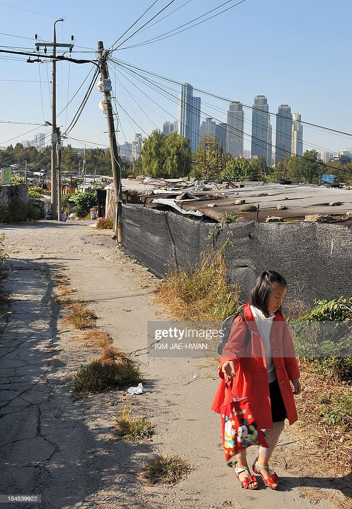 SKorea-society-poverty,FEATURE by Lim Chang-Won This photo taken on October 11, 2012 shows a South Korean elementary school girl walking on a road lined by a cluster of shacks in Guryong Village against the background of high-rise business buildings in Seoul. Guryong -- a squalid, sprawling slum of plywood and tarpaulin shacks settled in 1988 by squatters evicted from other areas in a push to beautify Seoul as it prepared to host the Olympic Games. Nearly 25 years later, Guryong (which translates as 'Nine Dragons') has more than 2,000 residents scrabbling out a subsistence living with Third World poverty levels and little or no proper sanitation.