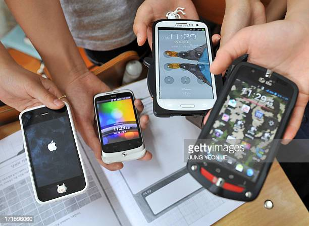 SKoreatechnologyITaddictionhealthFEATURE by JUNG HaWon This picture taken on June 11 2013 shows South Korean children displaying their smartphones...