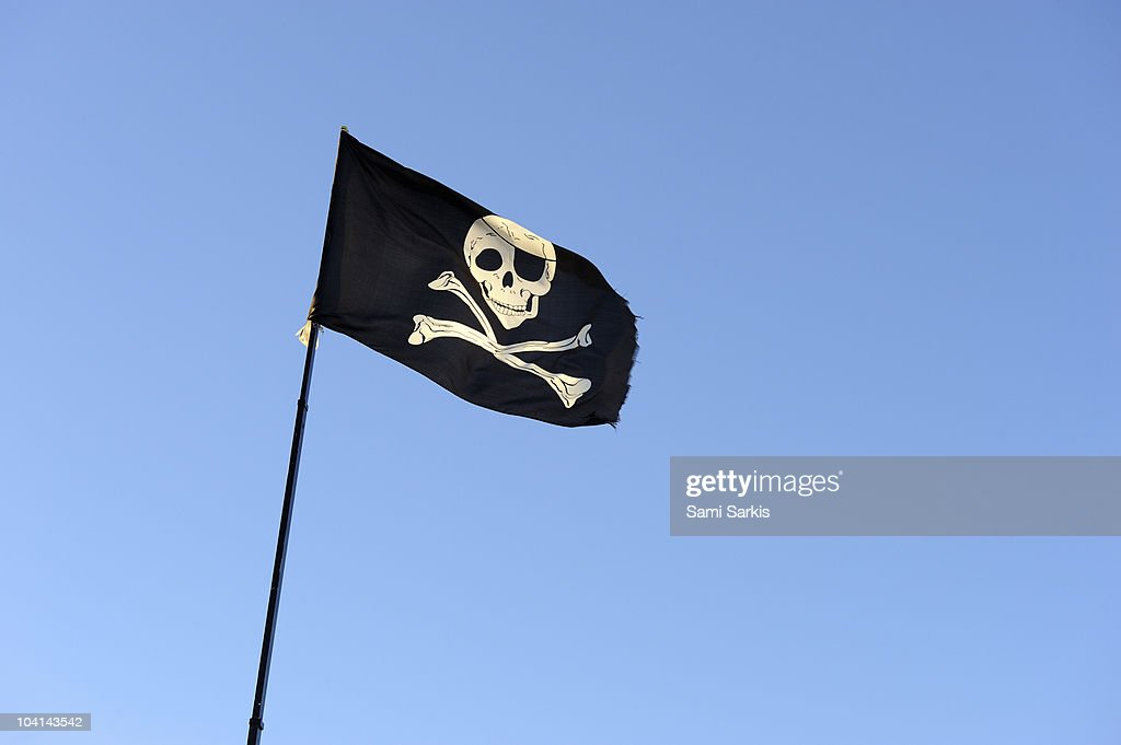 Skull and crossbones on Pirate's flag on blue sky : Stock Photo