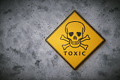 A square yelow sign with the international symbol for poison and other chemical / biological hazard. The sign is set on a dirty concrete wall surface.