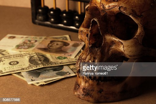 skull on old wood with banknote yuan and dollar : Stock Photo