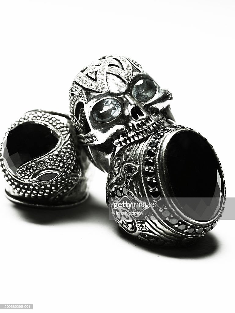 Skull-shaped ring on top of two rings with black stone, close-up : Stock Photo