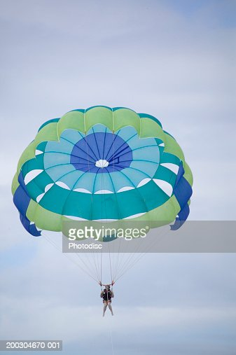 Sky diver coming down from sky in parachute, low angle view