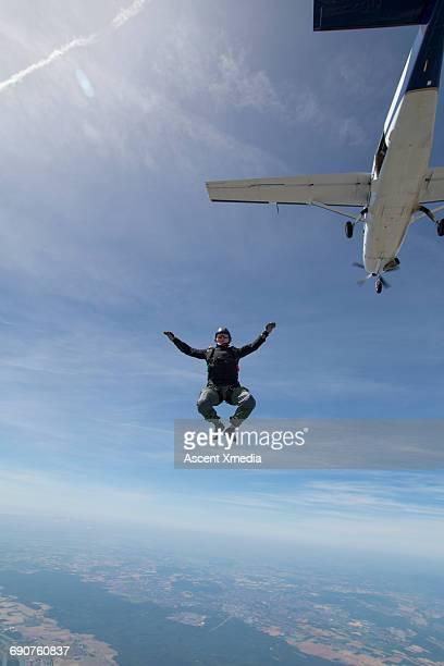 Sky diver in free fall below plane, above lake
