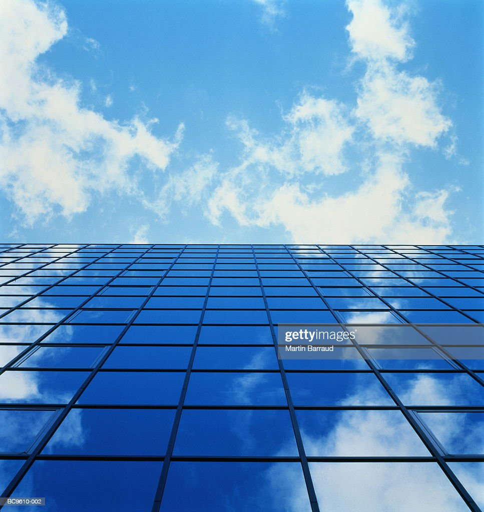 Sky reflected in windows of skyscraper, low angle view : Stock Photo