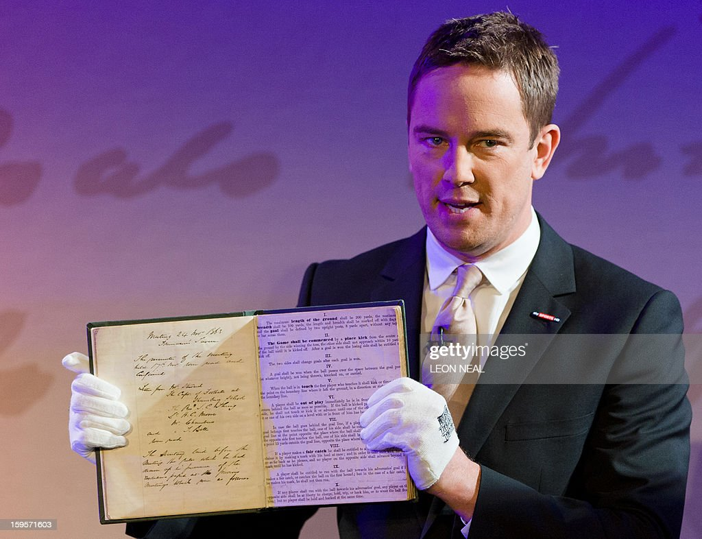 Sky Sports presenter Simon Thomas holds the original English Football Association (FA) minute book during the 'FA 150' event on January 16, 2013 in central London, to mark the 150th anniversary of the founding of the Football Association. The event saw figures from all areas of English football joined by international football stars to celebrate the anniversary. AFP PHOTO/Leon NEAL