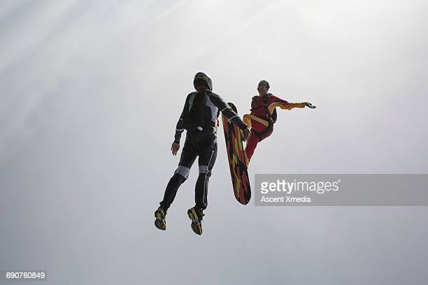 Sky surfer & companion in free fall through clouds