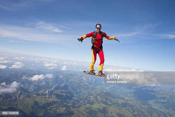 Sky surfer in freefall above mountain landscape