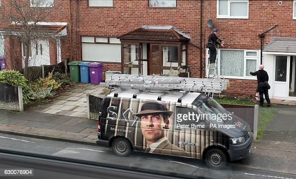 A Sky television engineer installs a satellite dish at an address in Liverpool