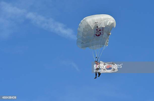 A skydiver carrying the South Korean flag lands on the 18th green during the prize giving cermony after the final round of The Evian Championship at...