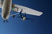 Skydiver exiting a small airplane