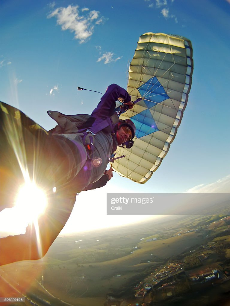 Skydiver flying at sunset with lens flare .
