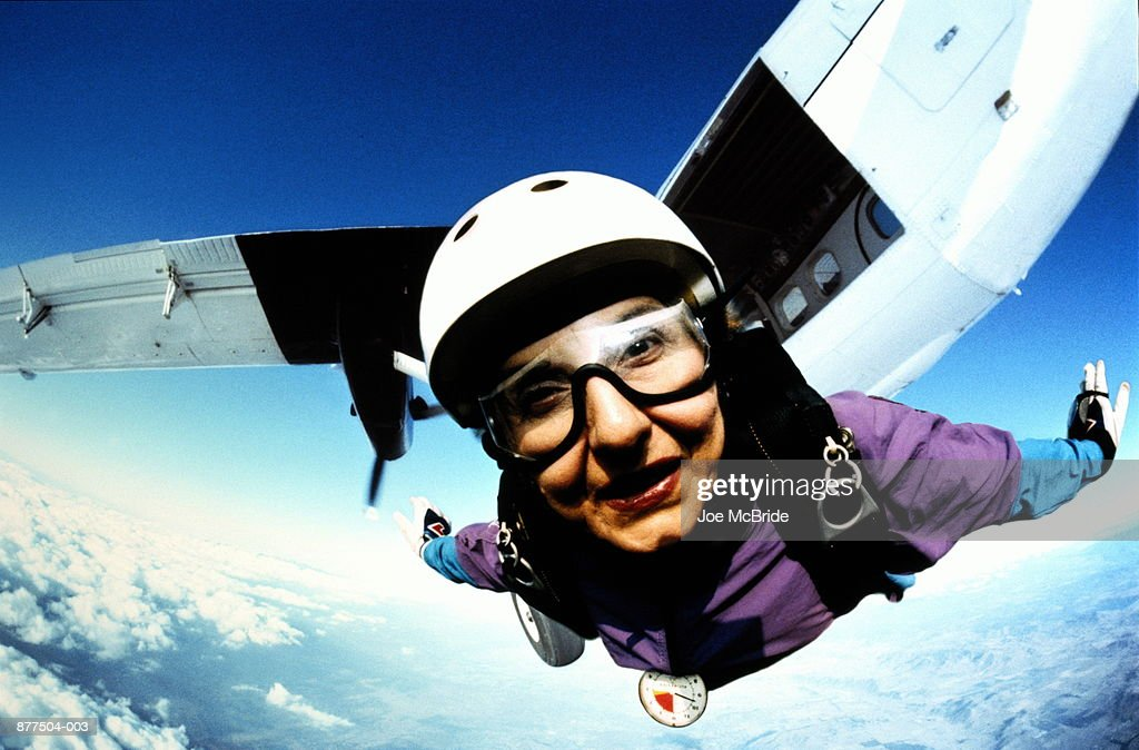 Skydiver flying in mid-air, plane in background, close-up