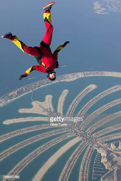 Skydiver flying upside down above the Dubai palm