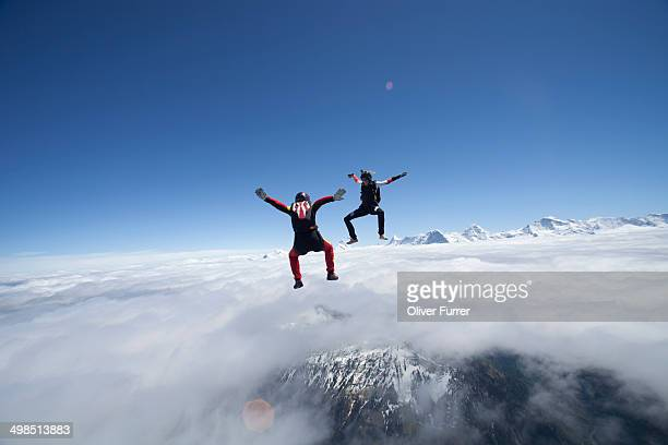 Skydiver girls dancing over clouds in the sky