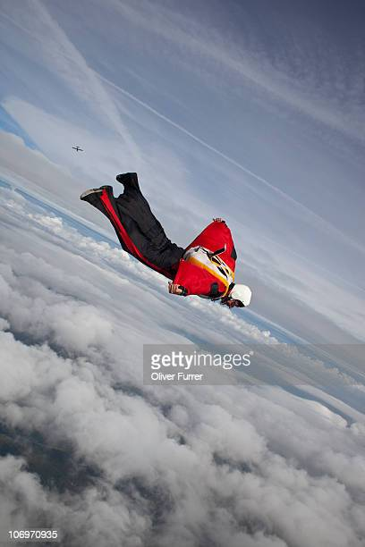 Skydiver in special wingsuit is flying over clouds