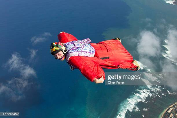 Skydiver is flying within a wingsuit over clouds