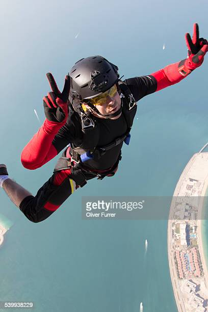 Skydiver over Dubai with peace sign
