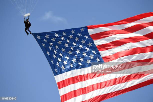 A skydiver parachutes the American Flag into the stadium during a college football game between the Hawai'i Rainbow Warriors and the UCLA Bruins on...