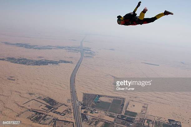 Skydiver tracking in the sky over a desert area