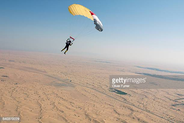 Skydiver under canopy flying over a desert area