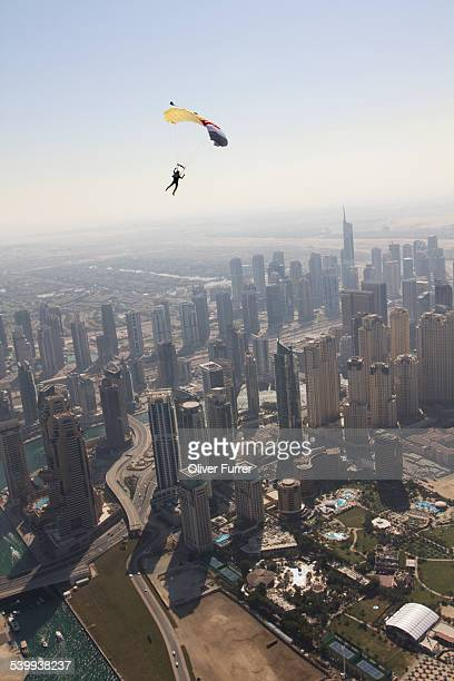 Skydiver under canopy flying over Dubai city