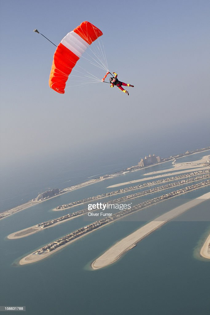 Skydiver under canopy soaring above the beaches : Stock Photo