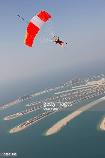 Skydiver under canopy soaring above the beaches