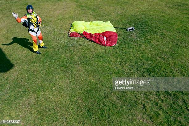 Skydiver waving after a save grass landing